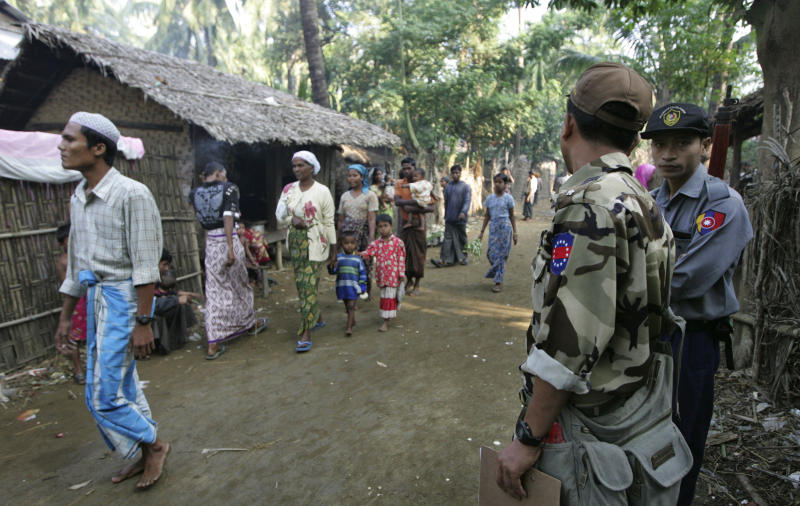 In this photo taken on Nov. 10, 2012, Muslim refugees walk as Myanmar police officers stand guard at Sin Thet Maw relief camp in Pauktaw township, Rakhine state, western Myanmar.  Myanmar's government has launched a major operation aimed at verifying the citizenship of Muslims in western Rakhine state, the coastal territory that has been torn apart by Buddhist-Muslim violence since June.  Questions over whether the region's Muslim Rohingya population qualify for citizenship are at the heart of a crisis that has killed nearly 200 people and displaced 110,000 more.    (AP Photo/Khin Maung Win)