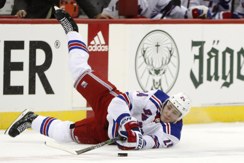 New York Rangers right wing Kaapo Kakko (24) reaches for the puck after falling during the second period of the team's NHL hockey game against the New Jersey Devils, Thursday, Oct. 17, 2019, in Newark, N.J. (AP Photo/Kathy Willens)