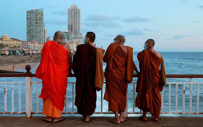 Buddhist monks wearing protective masks are seen on a deck at a beach, amid concerns about the spread of the coronavirus disease - Dinuka Liyanawatte/Reuters