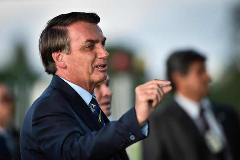 Brazils President Jair Bolsonaro greets his supporters and speaks to journalists amidst the coronavirus (COVID - 19) pandemic at the Presidential Residence, Alvorada Palace, in Brasilia, Brazil, on March, 31, 2020. Bolsonaro recently defended the nation's return to normality and the end of social distancing and quarantine. (Photo by Andre Borges/NurPhoto via Getty Images)