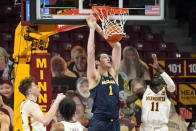 Michigan's Hunter Dickinson (1) dunks as Minnesota's Liam Robbins, left, Marcus Carr and Both Gach, right, watch during the first half an NCAA college basketball game, Saturday, Jan. 16, 2021, in Minneapolis. (AP Photo/Jim Mone)