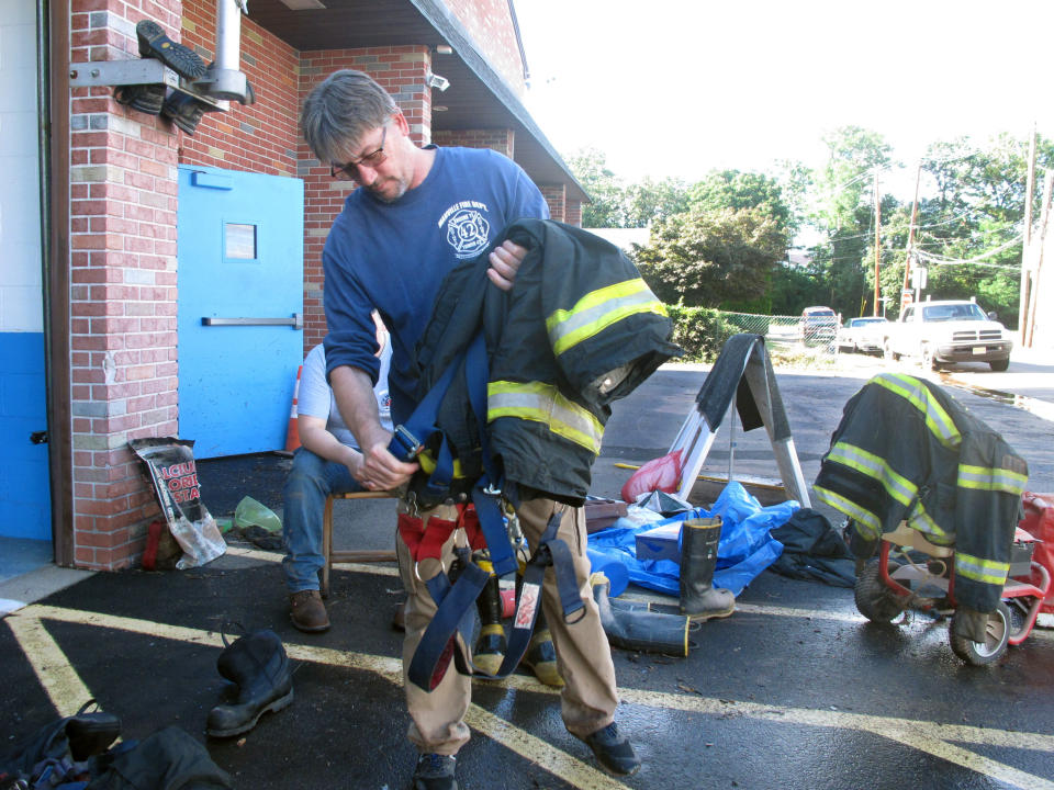Firefighter James Monto carries equipment out from a Manville N.J. firehouse Friday, Sept. 3, 2021 after the building was flooded with four feet of water during Tropical Storm Ida. (AP Photo/Wayne Parry)