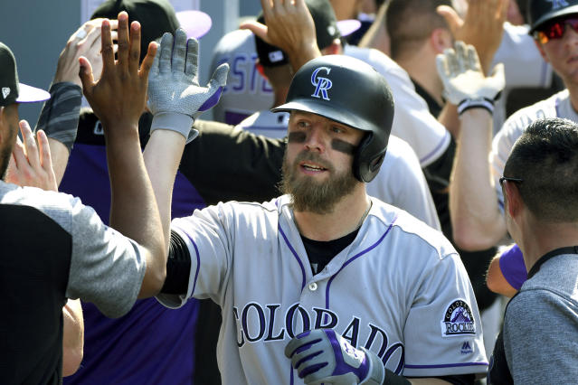 FILE - In this Sunday, Sept. 10, 2017 file photo, Colorado Rockies' Mark Reynolds is congratulated in the dugout after hitting a grand slam in the eighth inning of a baseball game against the Los Angeles Dodgers in Los Angeles. First baseman Mark Reynolds says he has agreed to a minor-league contract with the Colorado Rockies, Wednesday, Jan. 30, 2019. The 35-year-old Reynolds spent 2016 and 17 with the Rockies before joining Washington last season. (AP Photo/Michael Owen Baker, File)