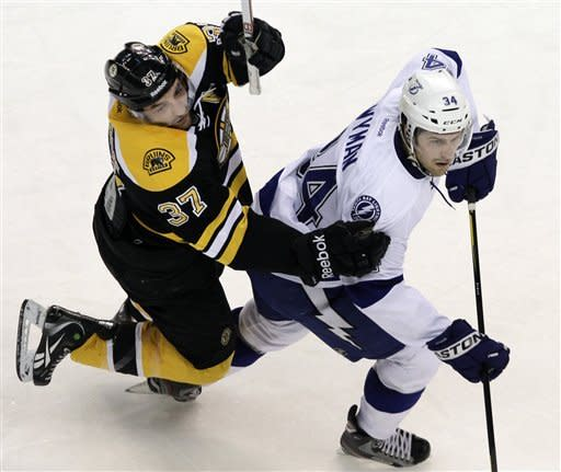 Boston Bruins center Patrice Bergeron (37) fights for position with Tampa Bay Lightning right wing J.T. Wyman (34) in the first period of an NHL hockey game in Boston, Tuesday, March 27, 2012. (AP Photo/Elise Amendola)