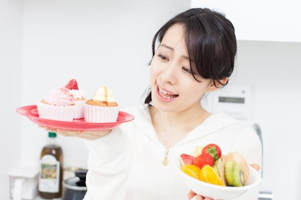 Smiling young woman holding cupcake and fruits