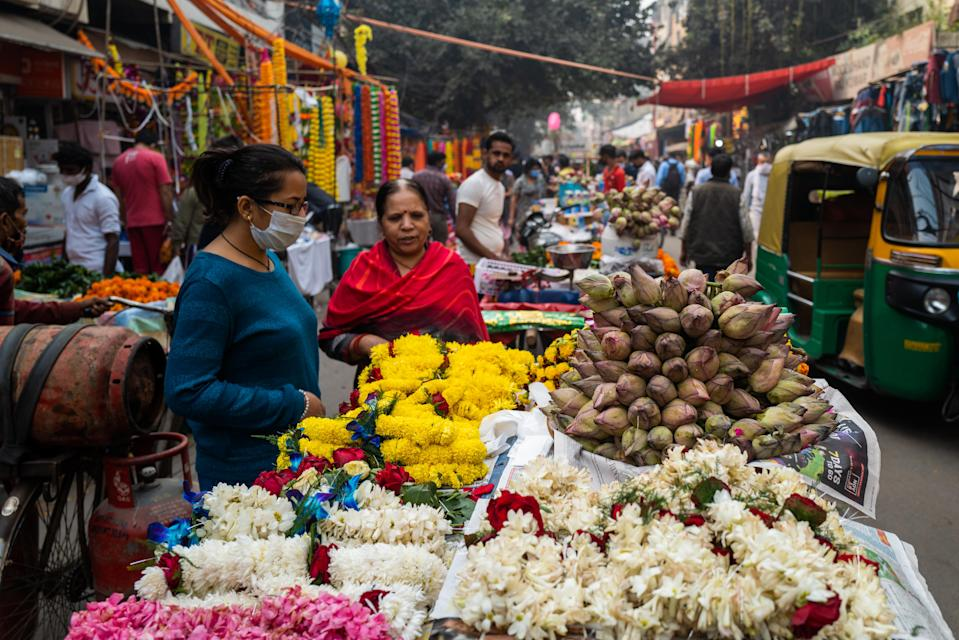 People buy flowers for Diwali, the Hindu Festival of Lights, from a vendor in a market area in New Delhi on November 14, 2020.