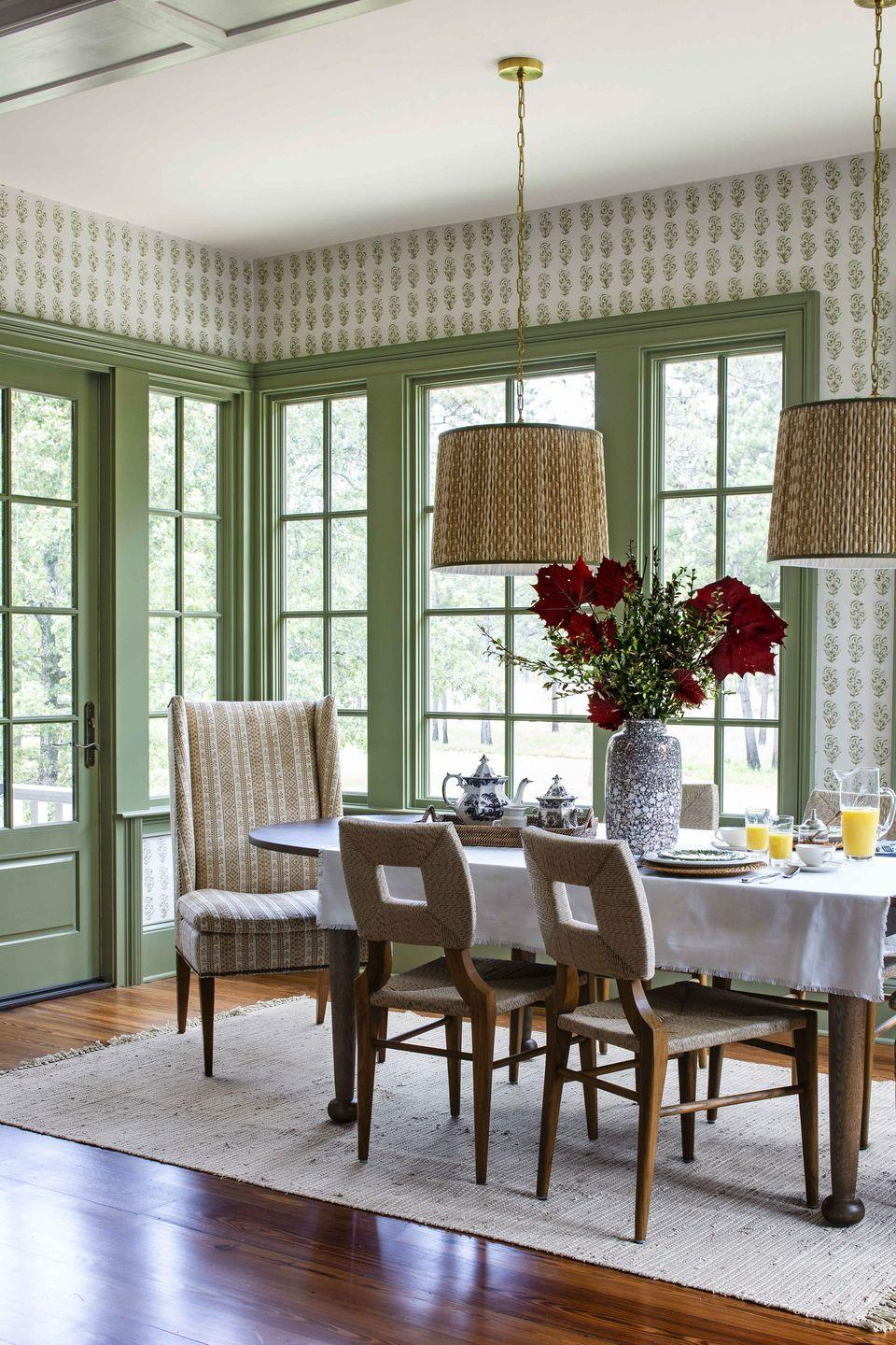 """<p>The coziness of verdant block-print wallpaper (<a href=""""https://lesindiennes.com/"""" rel=""""nofollow noopener"""" target=""""_blank"""" data-ylk=""""slk:Les Indiennes"""" class=""""link rapid-noclick-resp"""">Les Indiennes</a>) and a textured rug (<a href=""""https://annieselke.com/c/dashandalbert"""" rel=""""nofollow noopener"""" target=""""_blank"""" data-ylk=""""slk:Dash & Albert"""" class=""""link rapid-noclick-resp"""">Dash & Albert</a>) welcomes guests to mingle and enjoy the incredible views from this <a href=""""https://www.veranda.com/decorating-ideas/a29416524/andrew-howard-south-caroline-home-tour/"""" rel=""""nofollow noopener"""" target=""""_blank"""" data-ylk=""""slk:South Carolina breakfast room"""" class=""""link rapid-noclick-resp"""">South Carolina breakfast room</a>. Designer <a href=""""http://www.andrewjhoward.com/"""" rel=""""nofollow noopener"""" target=""""_blank"""" data-ylk=""""slk:Andrew Howard"""" class=""""link rapid-noclick-resp"""">Andrew Howard</a> paired the rustic side chairs from <a href=""""https://www.hollywoodathome.com/"""" rel=""""nofollow noopener"""" target=""""_blank"""" data-ylk=""""slk:Hollywood at Home"""" class=""""link rapid-noclick-resp"""">Hollywood at Home</a> with a host chair covered in <a href=""""https://www.michaelsmithinc.com/furniture-and-fabrics/fabrics"""" rel=""""nofollow noopener"""" target=""""_blank"""" data-ylk=""""slk:Jasper"""" class=""""link rapid-noclick-resp"""">Jasper</a> fabric. </p>"""
