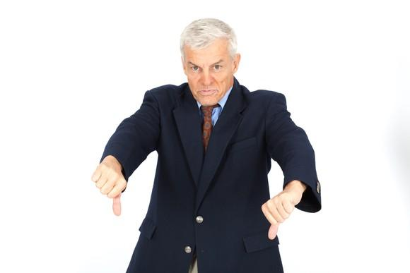 An executive in a suit giving the thumbs-down sign with both hands.