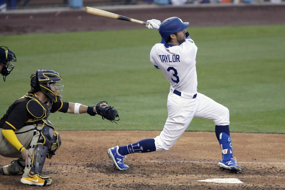 Dodgers second baseman Chris Taylor follows through to hit a three-run home run in front of Padres catcher Victor Caratini.