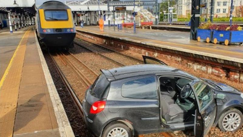 Two people in hospital after car lands on train tracks at station
