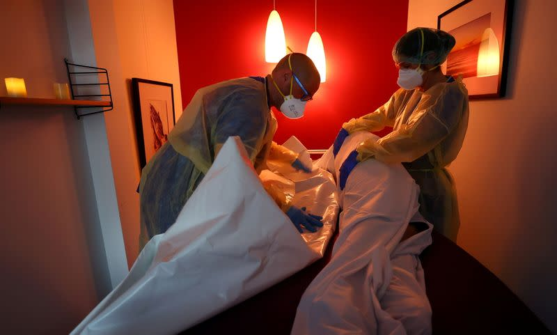 FILE PHOTO: Medical personnel prepares the body of a patient who died of COVID-19 at a clinic in Darmstadt