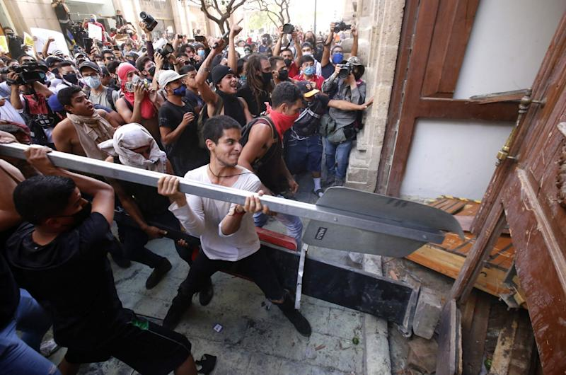 Demonstrators smash a door during a protest following the death of a young man while in police custody in Guadalajara, Mexico: AFP via Getty Images