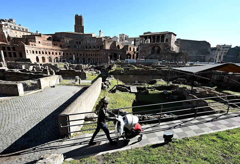 A man pushes a pram as he walks along the Foro Traiano Roman ruins in Rome on March 12, 2020 in Rome, as Italy shut all stores except for pharmacies and food shops in a desperate bid to halt the spread of a coronavirus that has killed 827 in the the country in just over two weeks. (Photo by Vincenzo PINTO / AFP) (Photo by VINCENZO PINTO/AFP via Getty Images)