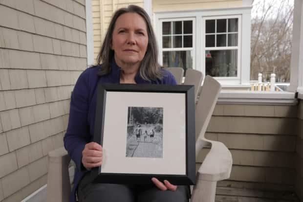 Dianne Taylor holds a photo of her with her late husband, Tim Taylor, and their daughter. Tim died suddenly of cancer in August 2018. (Dave Laughlin/CBC - image credit)