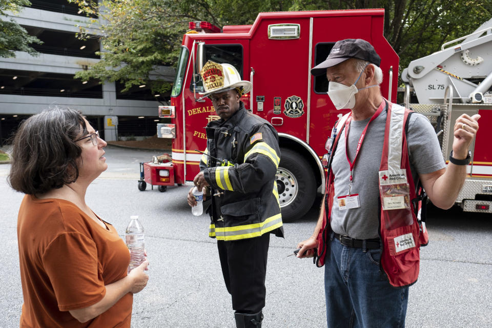 Dunwoody Mayor Lynn Deutsch, left, talks with a Red Cross worker as emergency workers respond following an apartment explosion, Sunday, Sept. 12, 2021, in Dunwoody, Ga., just outside of Atlanta. (AP Photo/Ben Gray)