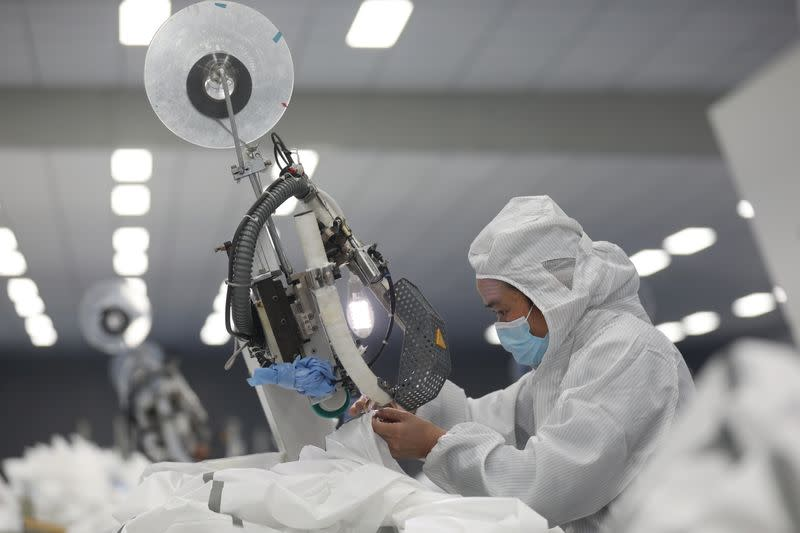 Employee works on a production line manufacturing protective suits at a medical supply factory in Xinzhou district of Wuhan