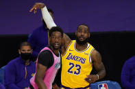 Los Angeles Lakers forward LeBron James, right, and Miami Heat center Bam Adebayo watch a shot by James that missed during the first half of an NBA basketball game Saturday, Feb. 20, 2021, in Los Angeles. (AP Photo/Mark J. Terrill)