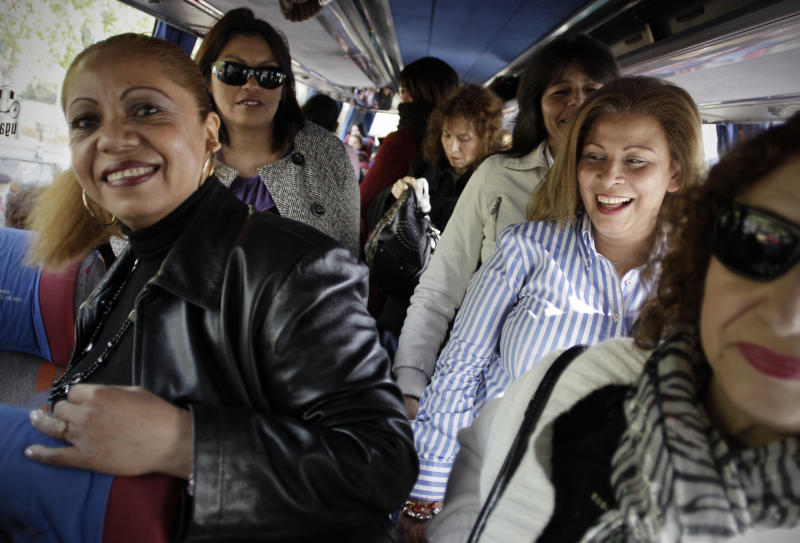 In this photo taken Saturday April 21, 2012, a group of women arrive in a bus before a meeting between men and women at the village of Candeleda, central Spain. 68 women were bussed in to the village to meet with the local men with the hope that some will form relationships and settle in the village where the main population is male.  (AP Photo/Alberto Di Lolli)