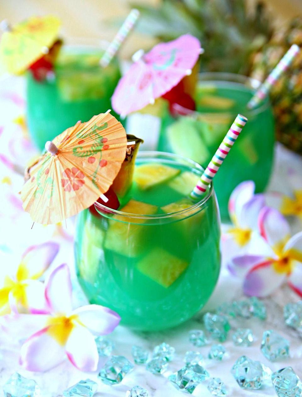 """<p>Mermaid water is a coconut- and pineapple- infused drink that gets its cool blue color from a splash of Blue Curaçao. Like any great tropical drink, it's best enjoyed with a <a href=""""https://www.amazon.com/KingSeal-Umbrella-Parasol-Cocktail-Cupcake/dp/B013KPL6LS/"""" rel=""""nofollow noopener"""" target=""""_blank"""" data-ylk=""""slk:tiki umbrella"""" class=""""link rapid-noclick-resp"""">tiki umbrella</a>. </p><p>Get the recipe at <a href=""""https://www.happygoluckyblog.com/mermaid-water-rum-punch/"""" rel=""""nofollow noopener"""" target=""""_blank"""" data-ylk=""""slk:Happy Go Lucky Blog"""" class=""""link rapid-noclick-resp"""">Happy Go Lucky Blog</a>. </p>"""