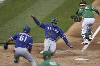 Texas Rangers Joey Gallo scores on a double hit by Todd Frazier against the Oakland Athletics during the fifth inning of a baseball game in Oakland, Calif., Tuesday, Aug. 4, 2020. (AP Photo/Jed Jacobsohn)