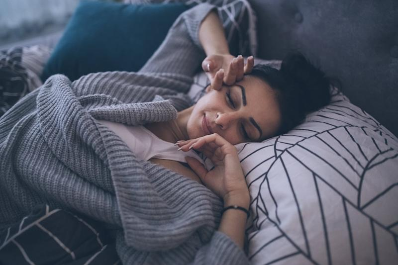 Young woman waking up at her own bed alone, with a smile