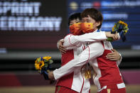 Shanju Bao, left, and Tianshi Zhong of Team China hug with their gold medals during a medal ceremony for the track cycling women's team sprint finals at the 2020 Summer Olympics, Monday, Aug. 2, 2021, in Izu, Japan. (AP Photo/Christophe Ena)