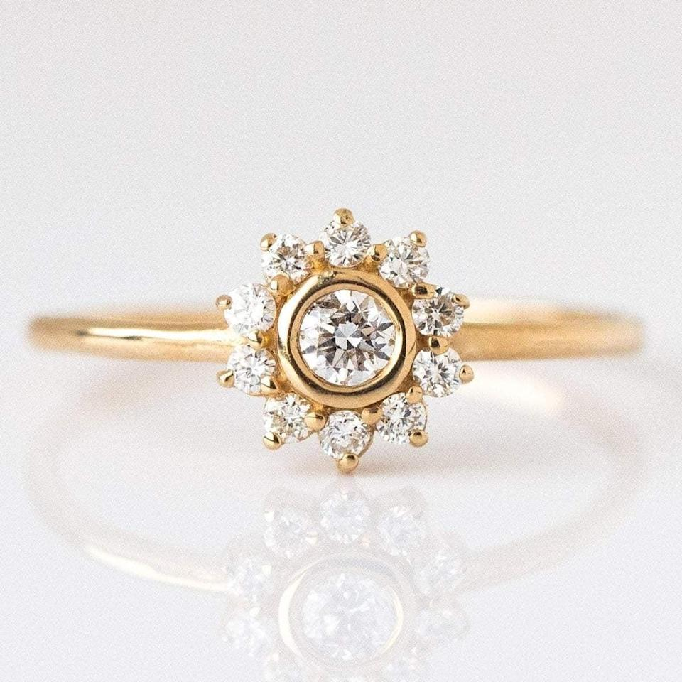 """<p>The trends of the 1980s are back, and they have brought back a resounding love for yellow gold all over again. This <a href=""""https://www.popsugar.com/buy/14k-Gold-Diamond-Sunflower-Ring-531760?p_name=14k%20Gold%20Diamond%20Sunflower%20Ring&retailer=localeclectic.com&pid=531760&price=520&evar1=fab%3Aus&evar9=7954958&evar98=https%3A%2F%2Fwww.popsugar.com%2Fphoto-gallery%2F7954958%2Fimage%2F47032814%2F14k-Gold-Diamond-Sunflower-Ring&list1=shopping%2Cwedding%2Cjewelry%2Crings%2Cengagement%20rings%2Cfashion%20shopping&prop13=api&pdata=1"""" rel=""""nofollow noopener"""" class=""""link rapid-noclick-resp"""" target=""""_blank"""" data-ylk=""""slk:14k Gold Diamond Sunflower Ring"""">14k Gold Diamond Sunflower Ring</a> ($520) encompasses the trend in a whole new kind of light.</p>"""