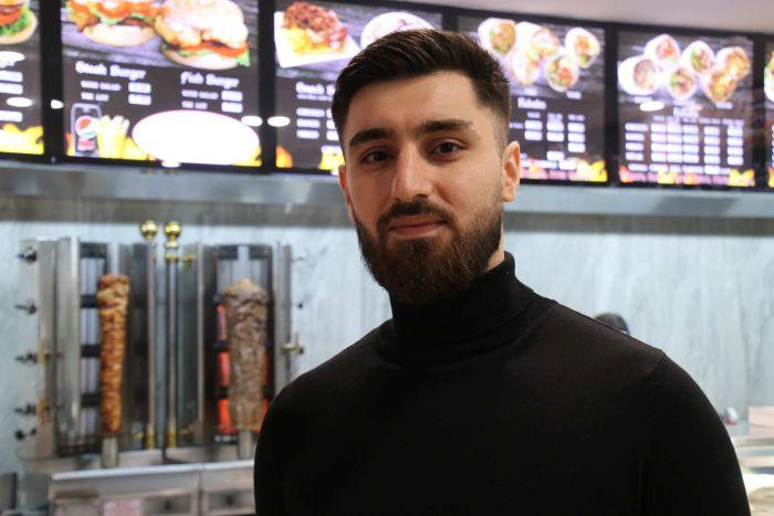 A head and shoulders shot of a man wearing a black turtleneck standing in a kebab shop looking at the camera.