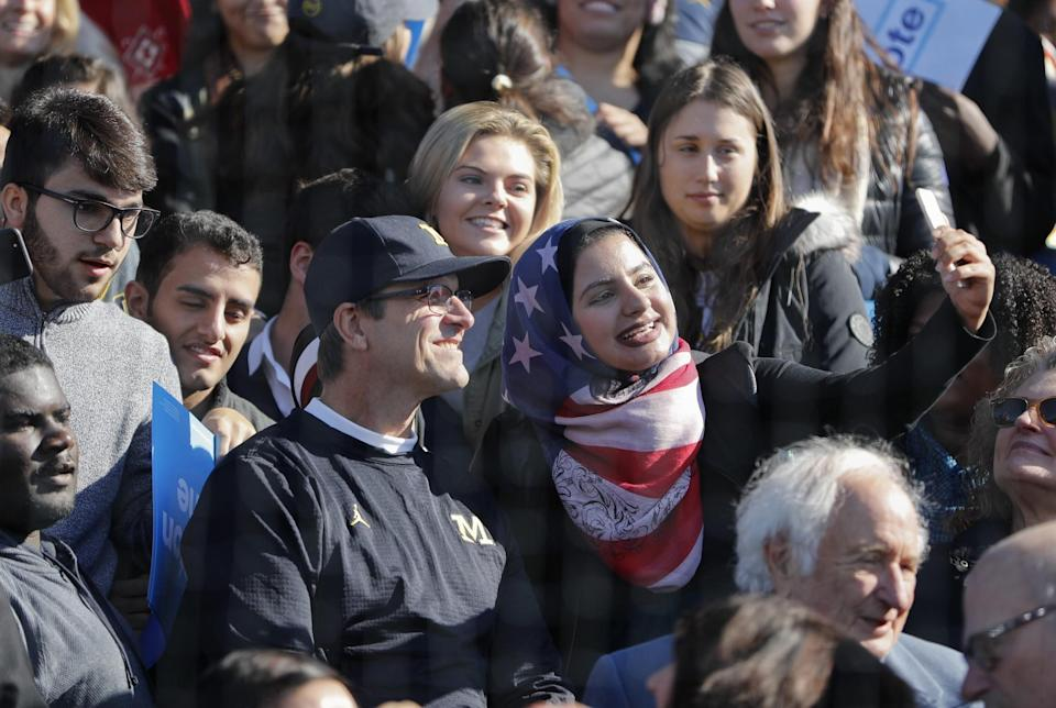 Michigan coach Jim Harbaugh takes pictures with fans following President Obama's rally for Hillary Clinton. (AP)