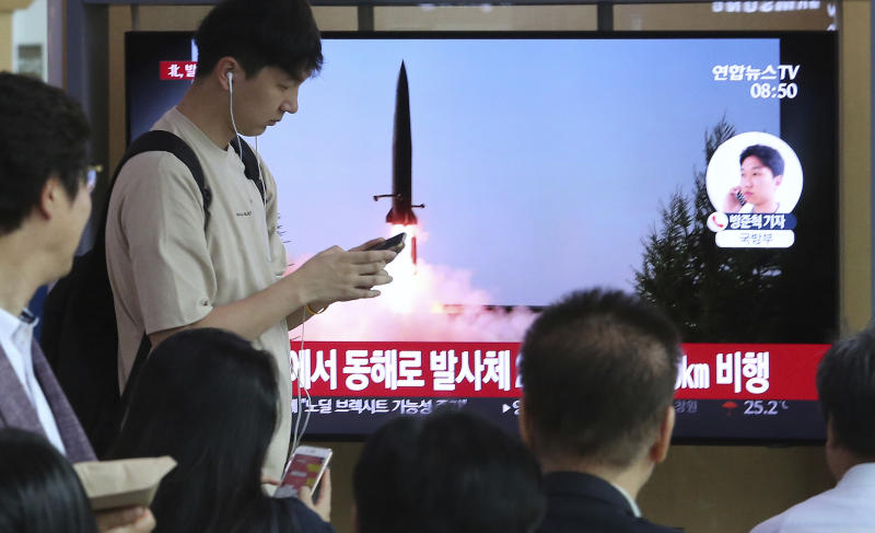 """People watch a TV showing a file image of North Korea's missile launch during a news program at the Seoul Railway Station in Seoul, South Korea, Thursday, July 25, 2019. North Korea fired two unidentified projectiles into the sea on Thursday, South Korea's military said, the first launches in more than two months as North Korean and U.S. officials work to restart nuclear diplomacy. The signs read: """"North Korea fired unidentified projectiles into the sea."""" (AP Photo/Ahn Young-joon)"""