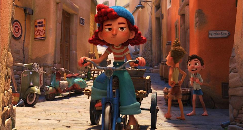 A redhaired girl rides her bicycle pulling a cart attached to the bike while two boys talk in the background