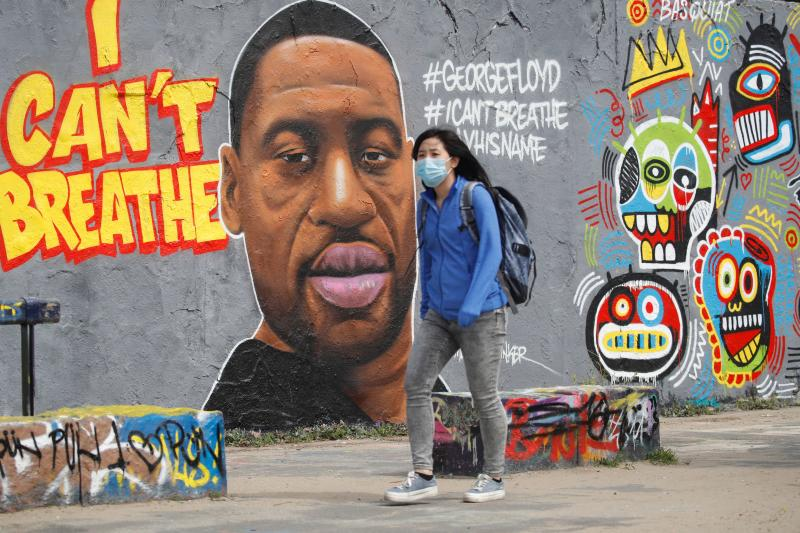 A woman wearing a protective mask walks past a graffiti depicting a portrait of George Floyd, a black man who died in Minneapolis after a white policeman kneeled on his neck for several minutes is seen in Berlin's Mauer Park on May 30, 2020. (Photo by Odd ANDERSEN / AFP) (Photo by ODD ANDERSEN/AFP via Getty Images)