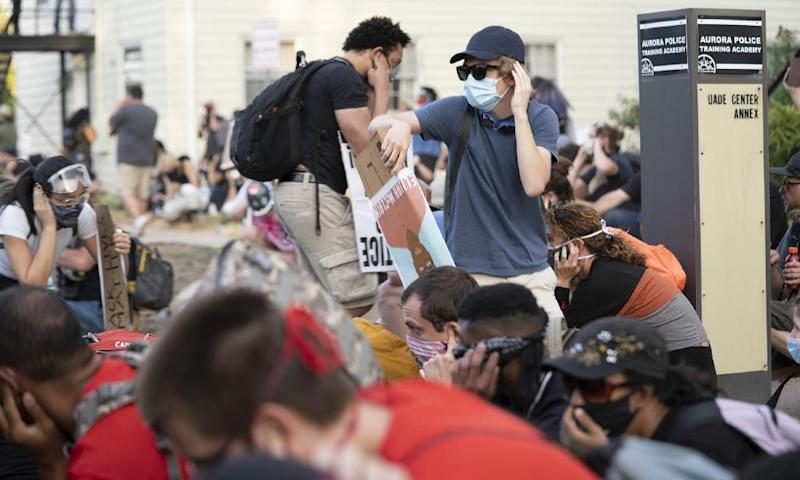 Demonstrators cover their ears as they expect police to deploy a long-range acoustic device on 3 July 2020, in Aurora, Colorado.