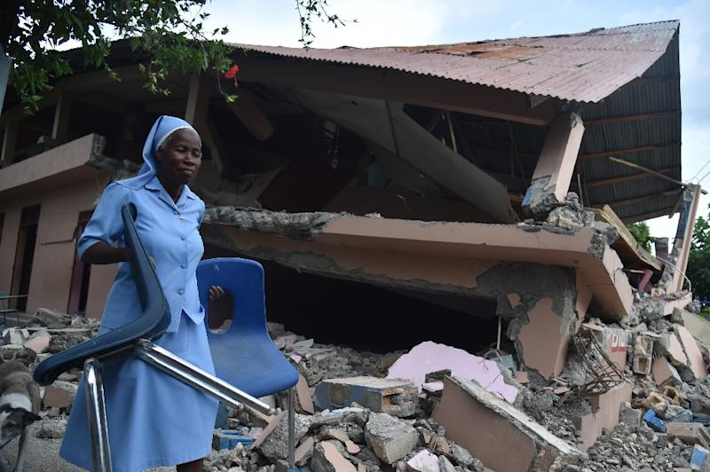 A nun carries chairs near a school damaged by a weekend earthquake in Haiti that has now left at least 17 people dead