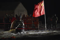 In this photo released by Xinhua News Agency, recovery crews look at the capsule of the Chang'e 5 probe after its successful landing at the main landing site in Siziwang district, north China's Inner Mongolia Autonomous Region on Thursday, Dec. 17, 2020. A Chinese lunar capsule returned to Earth on Thursday with the first fresh samples of rock and debris from the moon in more than 40 years. (Peng Yuan/Xinhua via AP)