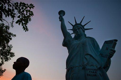 A man walks past a replica of the Statue of Liberty outside the People's Summit for Social and Environmental Justice in defense of the commons, a parallel event taking place alongside the United Nations Conference on Sustainable Development, or Rio 20, in Rio de Janeiro, Brazil, Sunday June 17, 2012. (AP Photo/Felipe Dana)
