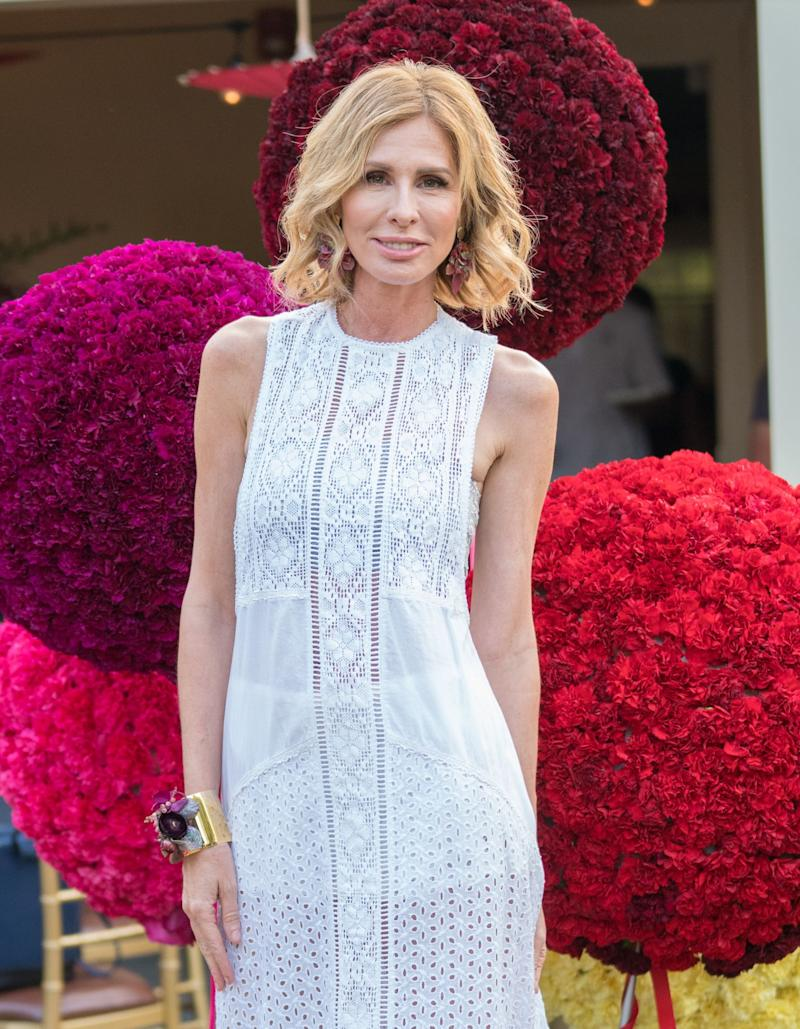 Carole Radziwill smiles posing in front of several trees made of flowers