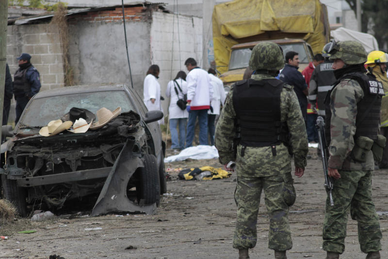 Soldiers guard the area as forensic workers gather evidence after a truck loaded with fireworks exploded during a religious procession in the town of Nativitas, Mexico, Friday March 15, 2013. A truck loaded with fireworks exploded during a religious procession in a rural village in central Mexico on Friday, killing at least nine people and injuring dozens more, authorities said. (AP Photo/J. Guadalupe Perez)