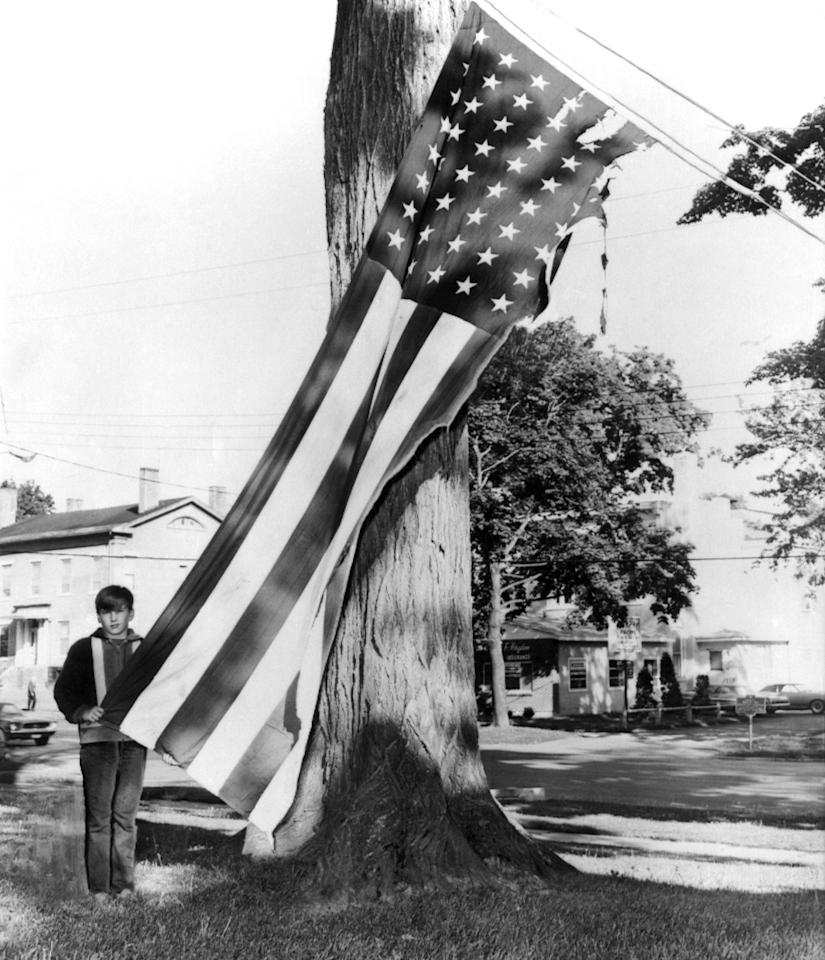 <p>This flag in front of the home of Andrew Tarby, a Marine combat veteran of Vietnam who came home from St. Albans Hospital for the holiday, was burned by vandals late Memorial Day night. His brother, Douglas, 10, looks at the flag, which was burned almost in half, May 31, 1969 in Auburn, New York. (AP Photo) </p>