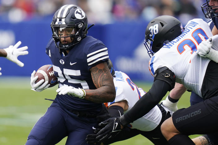BYU's Tyler Allgeier, left, carries the ball against Boise State in the first half during an NCAA college football game Saturday, Oct. 9, 2021, in Provo, Utah. (AP Photo/Rick Bowmer)