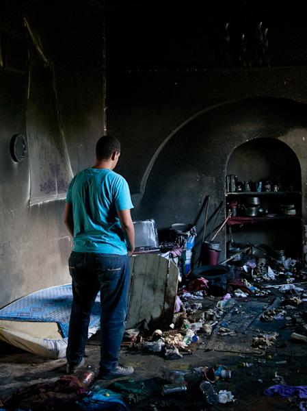A man stands among burnt items after masked individuals attacked and set fire to the popular 500-year-old shrine of Manouba, west of Tunis, early Tuesday, Oct.16, 2012. The shrine, which serves as a refuge for poor women, is also a place of symbolic worship for many Tunisians who visit the shrine bringing along food, money and candles. (AP Photo/Amine Landoulsi)