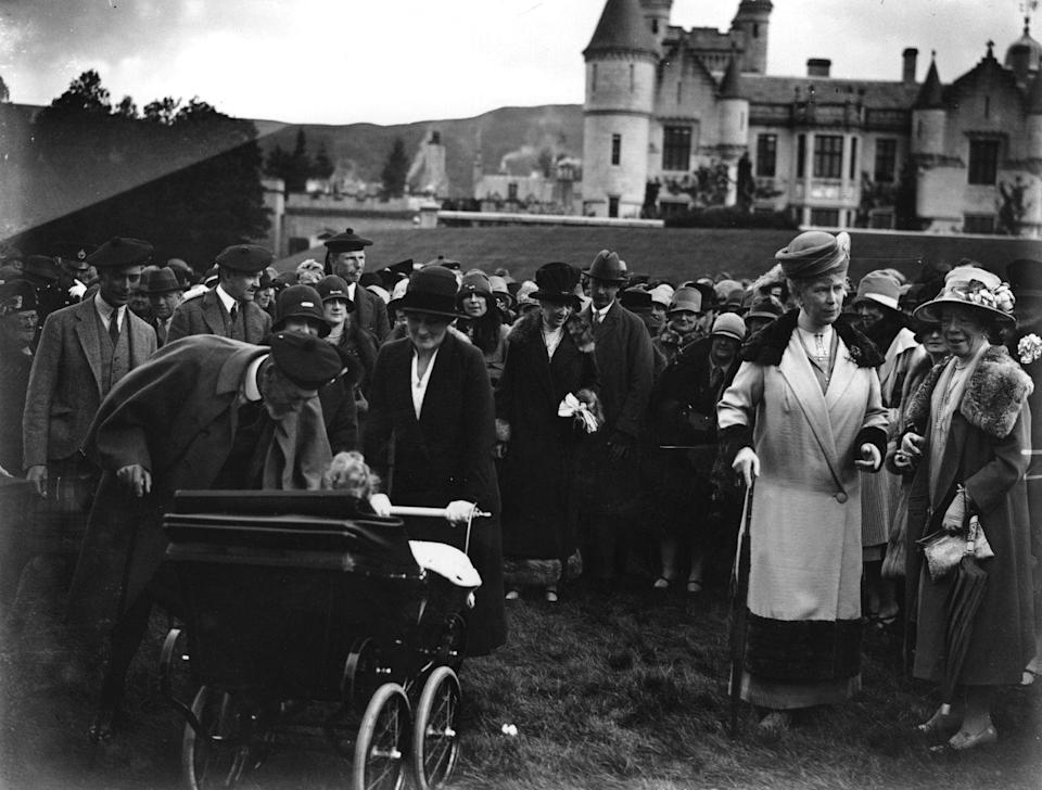 <p>This picture shows one of the modern Queen's earliest trips to Balmoral. The then-Princess Elizabeth is in the pram being doted on by her friends and family. While her father is on the far left side of the picture, her grandmother Queen Mary can be seen on the right-hand side.</p>