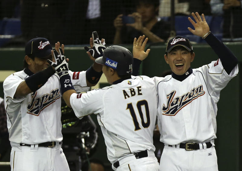 Japan's designated hitter Shinnosuke Abe (10) celebrates with teammates Seiichi Uchikawa, right, and Atsunori Inaba after hitting s a three-run homer off Netherlands' pitcher Jonatan Isenia in the second inning of their World Baseball Classic second round game at Tokyo Dome in Tokyo, Tuesday, March 12, 2013. (AP Photo/Toru Takahashi)