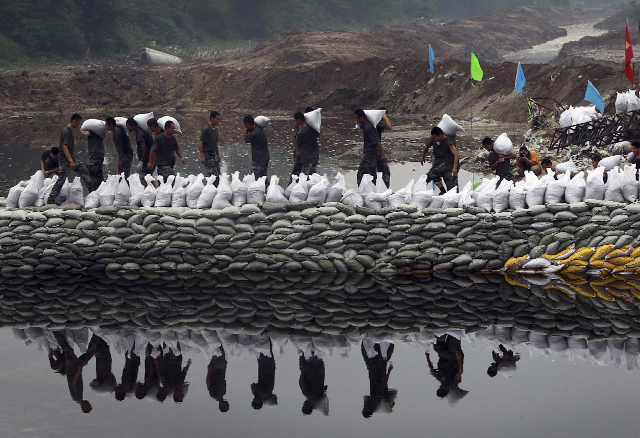 Chinese soldiers carry sandbags to build a makeshift dam to prevent flooding on Dongsha River in Fangshan district in Beijing, China Wednesday, July 25, 2012. Last Saturday's heavy rain was unusual in normally dry Beijing. On Wednesday, July 25 evening, more heavy rain fell on the capital as forecast by the Beijing Meteorological Bureau, which warned of possible flash flooding and mudslides in the capital's mountainous outskirts, including already hard-hit Fangshan. (AP Photo)