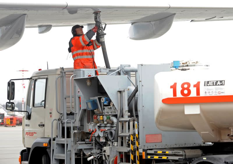 FILE PHOTO: A worker fills an Airbus jet with aviation fuel at Fuhlsbuettel airport in Hamburg