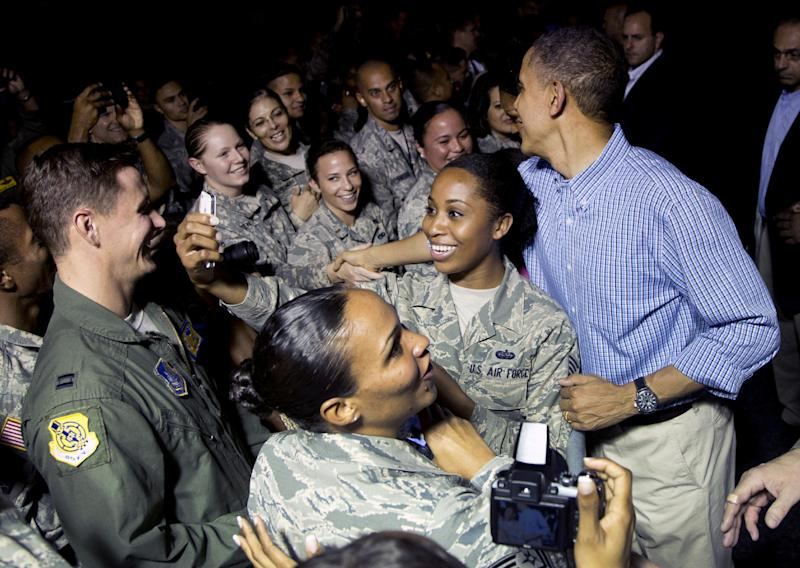 President Barack Obama greets members of the military waiting for him on the tarmac as he arrives with the first family on Air Force One at Joint Base Pearl Harbor-Hickam, in Honolulu, Friday, Dec. 20, 2013. The first family will be spending their annual winter vacation in Hawaii and return to Washington on Jan. 5, 2014. (AP Photo/Carolyn Kaster)