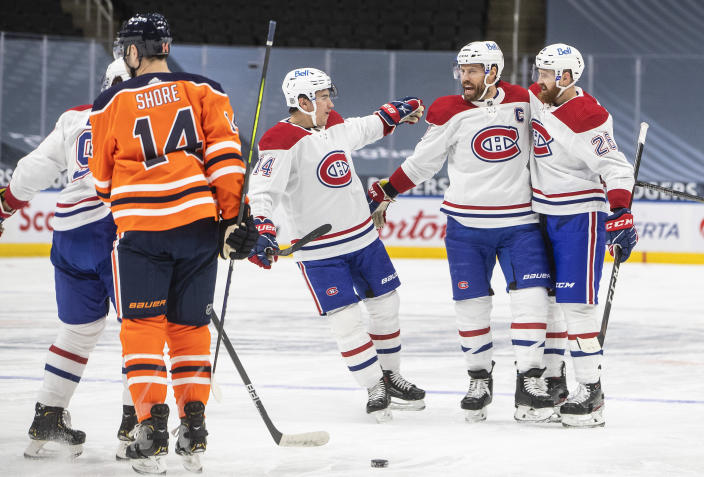 Edmonton Oilers' Devin Shore (14) skates past as Montreal Canadiens' Nick Suzuki (14), Shea Weber (6) and Jeff Petry (26) celebrate a goal during first-period NHL hockey game action in Edmonton, Alberta, Saturday, Jan. 16, 2021. (Jason Franson/The Canadian Press via AP)