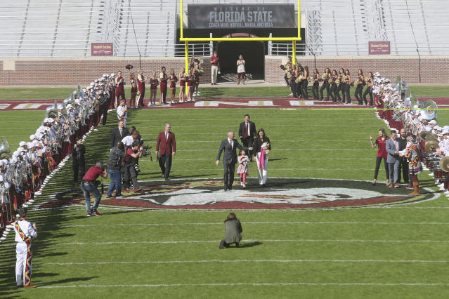 Florida State head football coach Mike Norvell, with daughter Mila and wife Maria, walks between rows of The Marching Chiefs as they play en route to a press conference Sunday, Dec. 8, 2019, in Tallahassee, Fla. Norvell is Florida States new coach, taking over a Seminoles program that has struggled while he was helping to build Memphis into a Group of Five power. (AP Photo/Phil Sears)