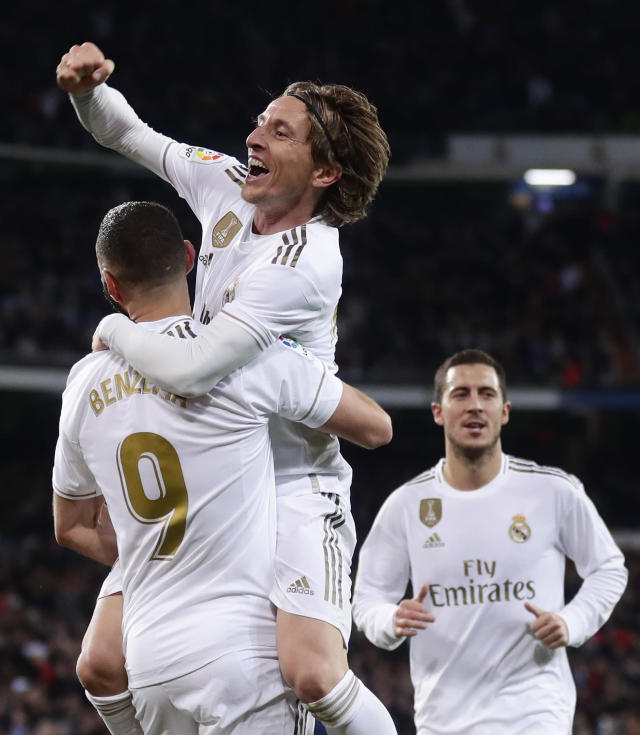 Real Madrid's Luka Modric celebrates with Karim Benzema after scoring his side's third goal during the Spanish La Liga soccer match between Real Madrid and Real Sociedad at the Bernabeu stadium in Madrid, Spain, Spain, Saturday, Nov. 23, 2019. (AP Photo/Manu Fernandez)