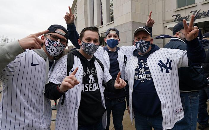 Fans pose in front of Yankee Stadium in New York on April 1, 2021 - TIMOTHY A. CLARY/AFP